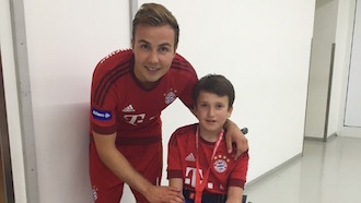 Mario Götze takes a picture with a child in a wheelchair