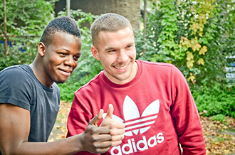 Lukas Podolski takes a picture with an African boy