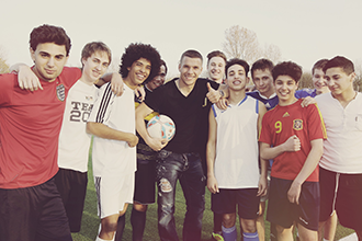 Lukas Podolski plays football with boys