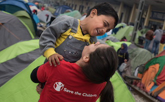 Save the children helper plays with refugee child