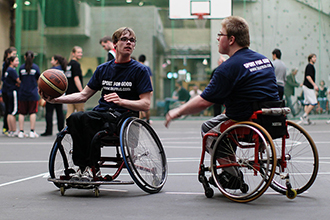 Two wheelchair users play wheelchair basketball